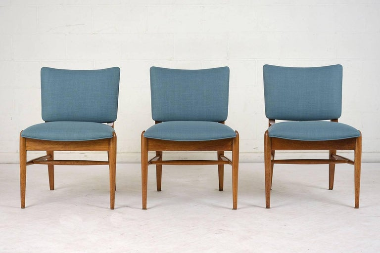 This set of six 1960s Mid-Century Modern dining chairs are designed by John Keal for Brown Saltman. The frames are made from teak wood stained a natural color with a polished finish. The chairs have stretched tapered legs and a boomerang shaped back