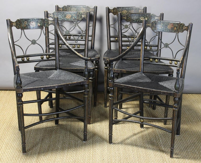 This exceptionally charming early 19th century American dining chairs are finely developed throughout with elegant lines, sturdy construction and beautiful paint and gilt decoration. Each crest rail is beautifully embellished with a unique hand