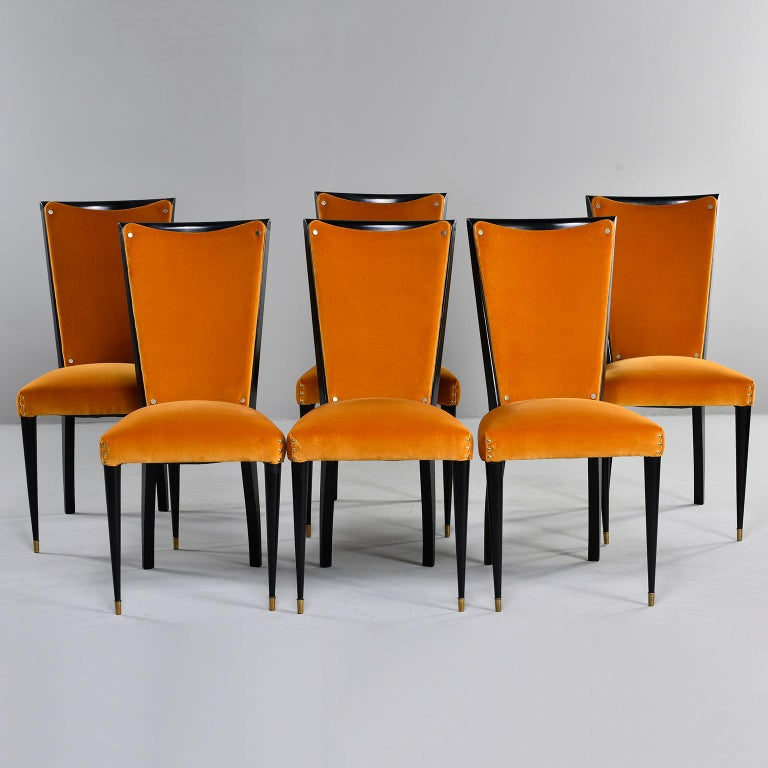 Set of six ebonised deco style dining chairs, circa 1940s. Chairs have tapered front legs with brass foot caps. Recently upholstered in poppy gold velvet that is in very good overall condition with virtually no signs of wear. Accented with brass