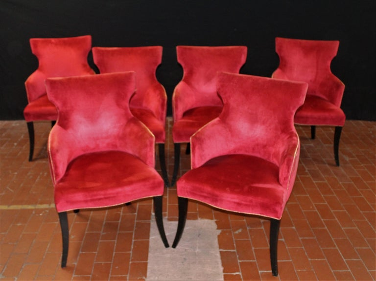 Set of 6 elegant dining chairs in a rich red velvet with gold welt detail on black lacquered cabriolet legs. The arm height is 25