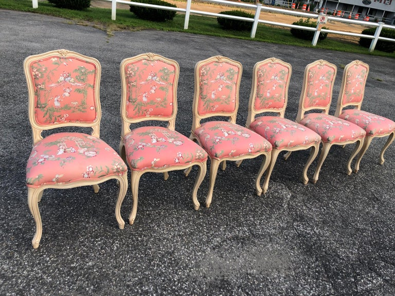 Set of 6 French Provincial chairs with Chinoiserie upholstery . Lovely pink and soft green, gray colors. Crème painted wooden trim. Elegant statement pieces for dining. Excellent condition.