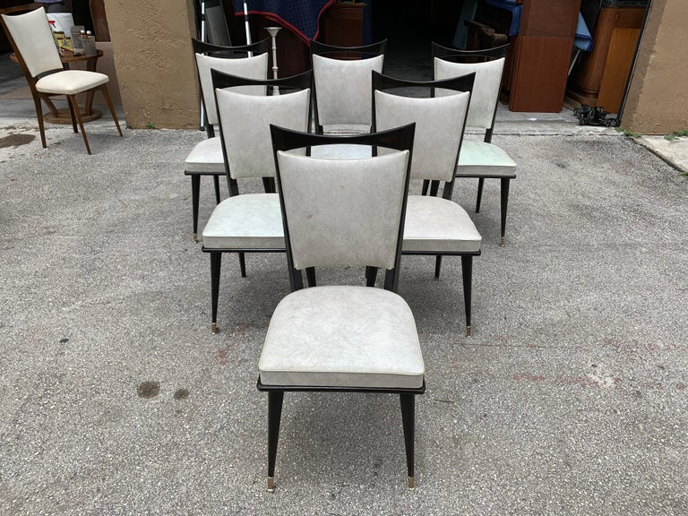 Classic set of six French vintage dining chairs solid mahogany, circa 1940s, the two front feet are capped with brass. The chair frames are in excellent condition. The Reupholstery is vinyl recommended to be change for all 6 dining chairs, the
