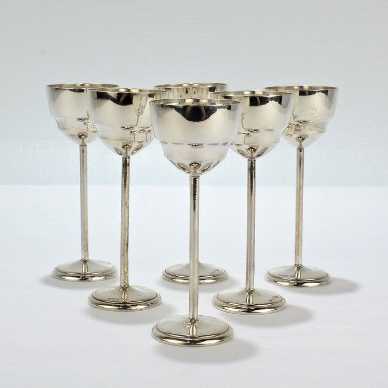 A fine set of 6 Art Deco silver cordials.   Elegantly simple with diminutive cups, straight stems and a round foot each.  The bases are marked with 800 for the silver fineness, a moon and crown for Germany, and KU for the maker.  Simply a crisp and