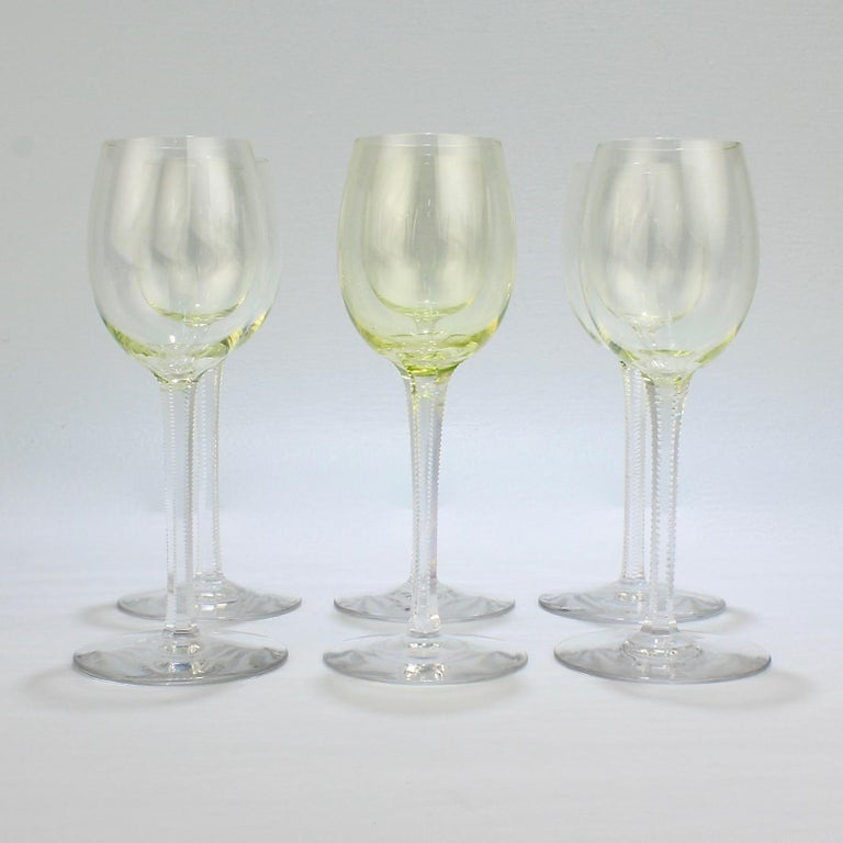 A fine group of 6 German or Austrian glass wine goblets dating to the early part of the 20th century.  Each with yellow-green (or Vaseline-glass color) tops and clear, wheel-cut, finely serrated stems.  Lovely to hold in the hand. Perfect for a