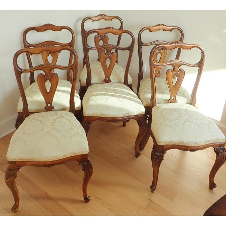 Set of 6 Italian Rococo Dining Room Chairs Hand carved walnut . 19th Century. Later damask upholstery.