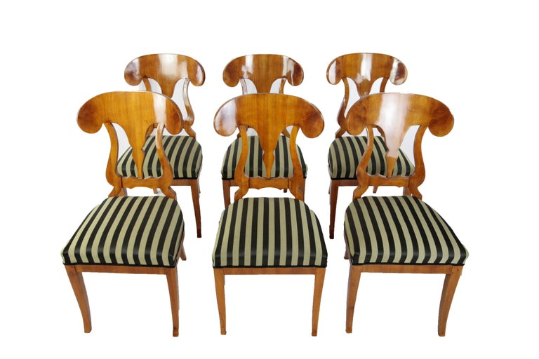 Set of 6 chairs made of cherrywood veneered, made circa 1850-1860 in Germany. The legs of the chairs are slightly concave. The seat of the chairs was newly upholstered and covered with a striped cotton-mix fabric. The backrests are moving in shape