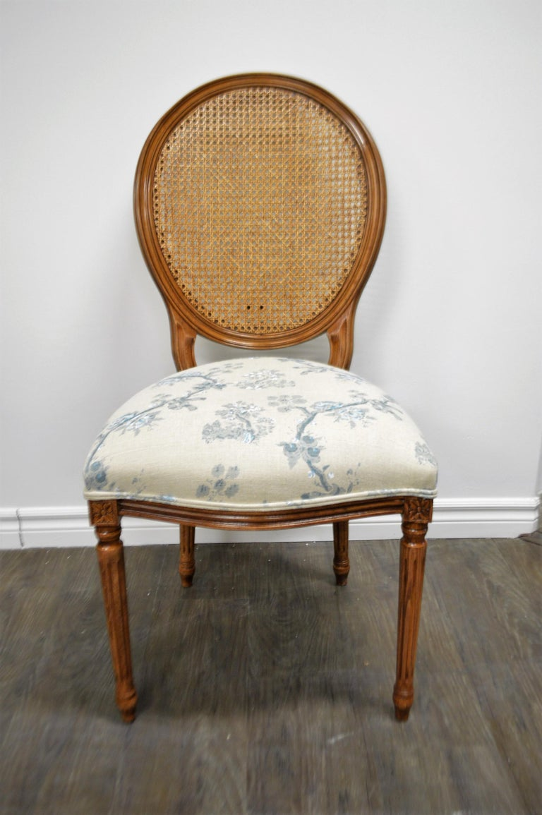 Set of 6 Louis XVI style oval back dining chairs. The chairs are made of beech wood in Italy, walnut stained. The fabric is a silk screen print on beige linen, in tones of light and darker blue with some white. More chairs of that style are