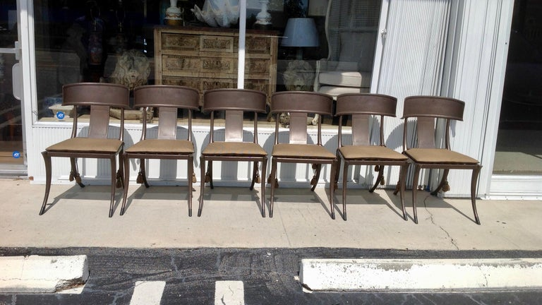 Michael Taylor cast aluminum Klismos chairs with metal basket wave seats. Bronze finish . Wonderfully curved legs and seat backs. The chairs can be used indoors or out. The chairs are outfitted with custom cushions appointed with tassels set of