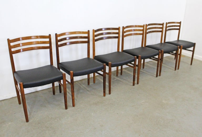 What a find. Offered is a vintage Mid-Century Modern set of rosewood dining chairs. These chairs have a beautiful rosewood grain and have been reupholstered with black leather. They are in good condition with some surface wear/scratches on the wood.