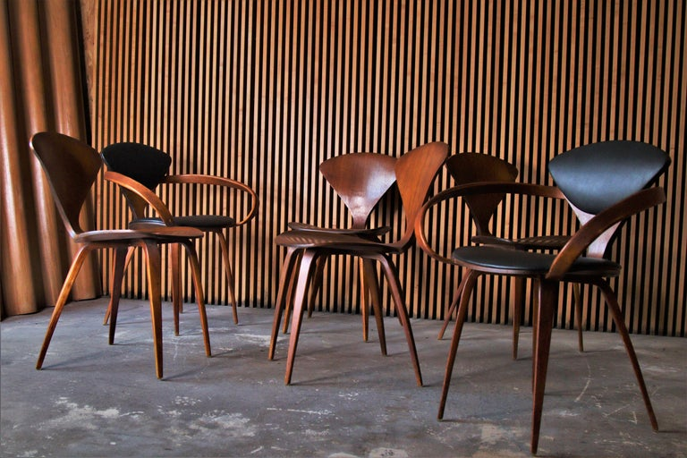 A set of 6 Pretzel dining chairs designed by Norman Cherner for Plycraft. The set consists of two armchairs with black leatherette upholstery and 4 upholstered walnut side chairs.  Dimensions: Armchairs 31