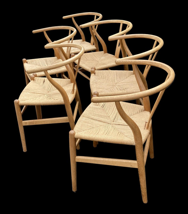 A beautiful set of these classic dining chairs by the master designer Hans J. Wegner and produced by Carl Hansen & Son, the wooden frames are in very good condition and are have golden oak patina, there are a few marks on the original papercord