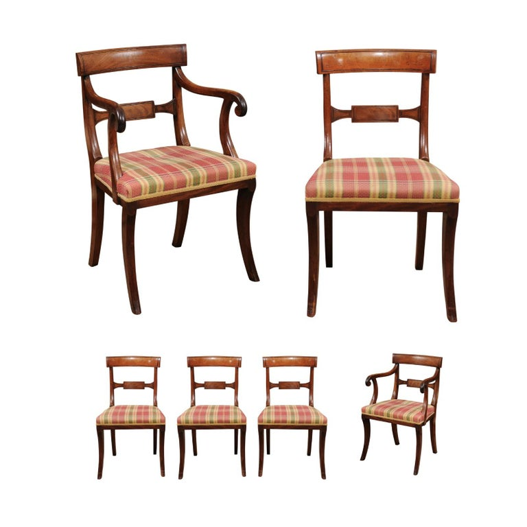 The set of 6 English Regency dining chairs with curved backs, scrolled arms (2 armchairs) and upholstered seats terminating in splayed legs.   Can be sold in pairs.  Dimensions for 2 armchairs - 34.5