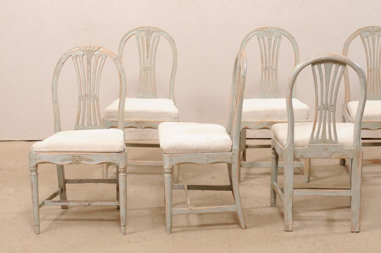 A Swedish set of six Provincial Gustavian wheat back side chairs from the early 19th century. These antique chairs from Sweden each feature nicely curved top rails with wheat-carved, pierced-splat backs, and gracefully scalloped skirts with a sweet