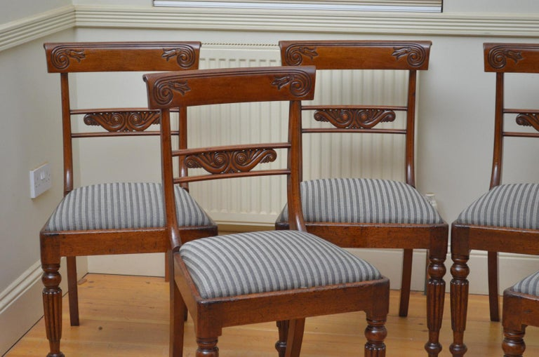 Sn4448, set of six mahogany dining chairs, each having shaped can carved top rails with finely carved mid rail below, drop in seat covered in complementary fabric, standing on turned and fluted legs. This set of antique dining chairs retains