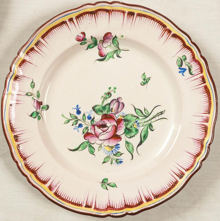 Set of 7 French faience plates, late 19th century. Beautiful hand painted floral design with combed border. Each plate has a slightly different design.