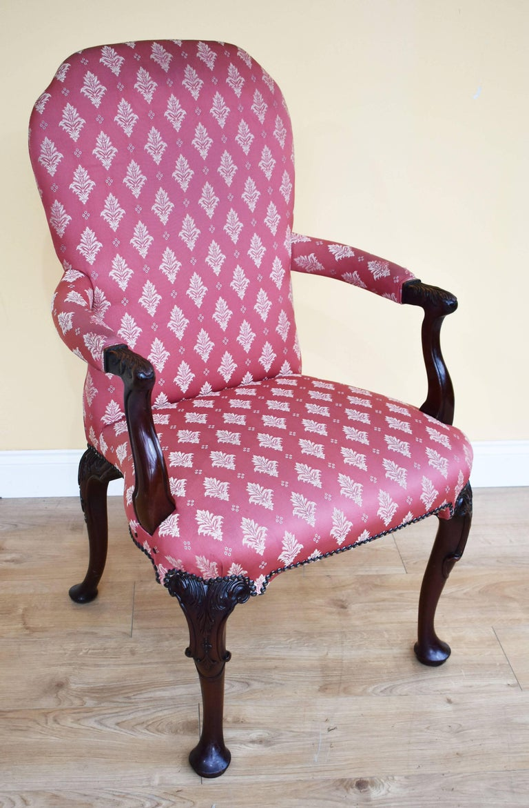 For sale is a good quality set of eight 18th century style mahogany open armchairs. Each having overstuffed backs and seats, the arms have floral leaf carvings. The chairs stand on cabriole front legs with bold leaf carved knees and pad feet.