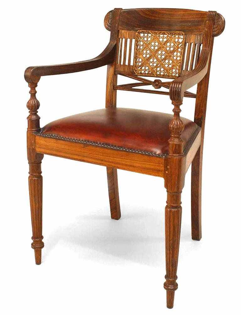 Set of eight twentieth century English Anglo-Indian hardwood armchairs with caned splats above leather upholstered seats and turned reeded legs.
