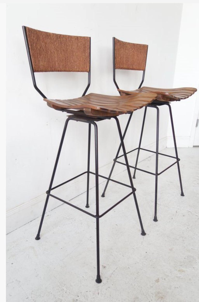 A set of four (4) clean-lined bar stools with wood slatted seat, rattan back and black metal base.  USA, circa 1950.  Priced at $737.50 per stool or $5,900 as a set of eight; contact us to specify a different quantity.  Dimebsions: 37