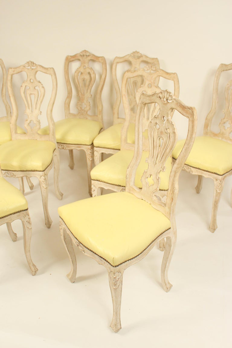 Set of 8 continental painted Louis XV style dining room chairs with light yellow vinyl seats, mid-20th century.