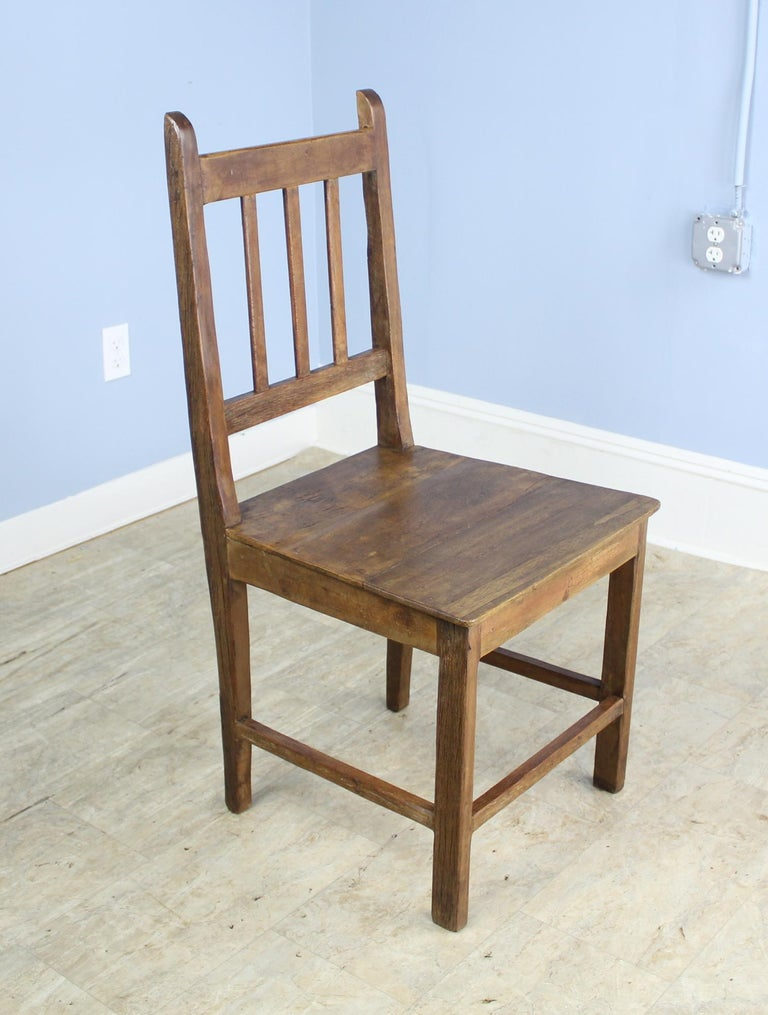 A charming set of English oak side chairs. A simple silhouette with lovely color and patina. The seats, pictured in images #6 and 7, have various degrees of wear, but all chairs are in sturdy good condition. Would look smart around a country farm