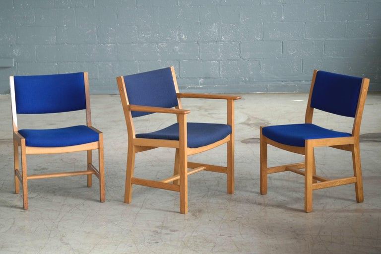 We love the angular modern clean lines of this set of Hans Wegner designed dining chairs produced by GETAMA of Denmark in the early 1970s. Manufactured from solid white oak and covered in blue wool fabric by Kvadrat. The set has seven side chairs