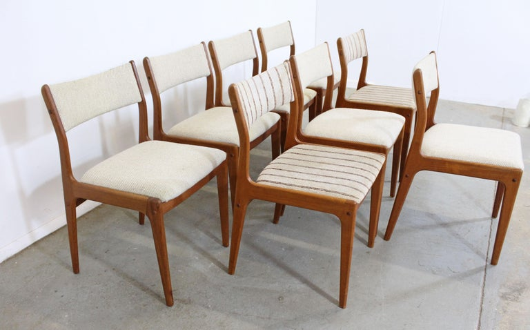 Offered is a set of 8 Danish Modern teak dining chairs designed by Johannes Andersen for Uldum Mobelfabrik. Includes 8 teak side chairs. The set is in vintage condition, need to be reupholstered, showing stains and tears on the fabric, a previous