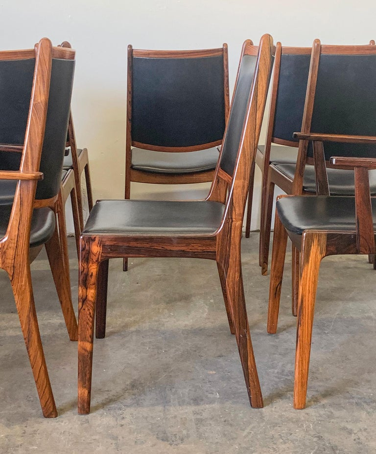 Available right now we have this stunning set of 8 Danish modern rosewood dining chairs. The rosewood grain on these chairs is absolutely stunning! Striking grain, and luxurious black leather make these chairs such sumptuous statement pieces.