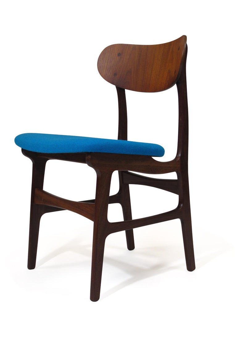 Eight midcentury Danish teak dining chairs with sculpted frames, topped off by bold and comfortable curved back supports. Chairs are newly upholstered in aqua blue wool. Finely restored. Measures: 19