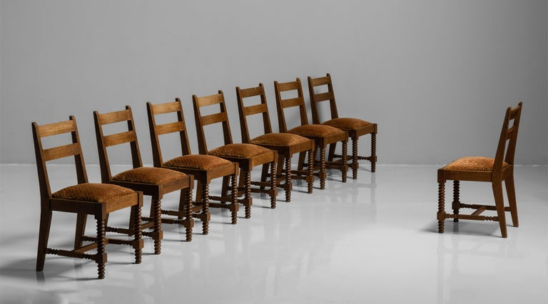 Set of (8) dining chairs attributed to Charles Dudouyt France, circa 1930  Carved oak frame with original velvet embroidered cushions.  Measures: 17.5