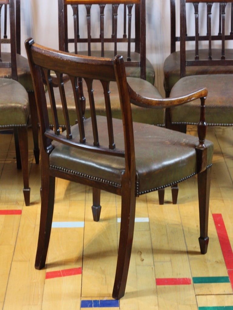 A superb set of 8 George III dining chairs, English carved mahogany. Federal backed with 5 carved fluted columns, the set includes 2 carvers with gently sloping arms. Upholstered in the original green leather with stud detailing. The bar back has