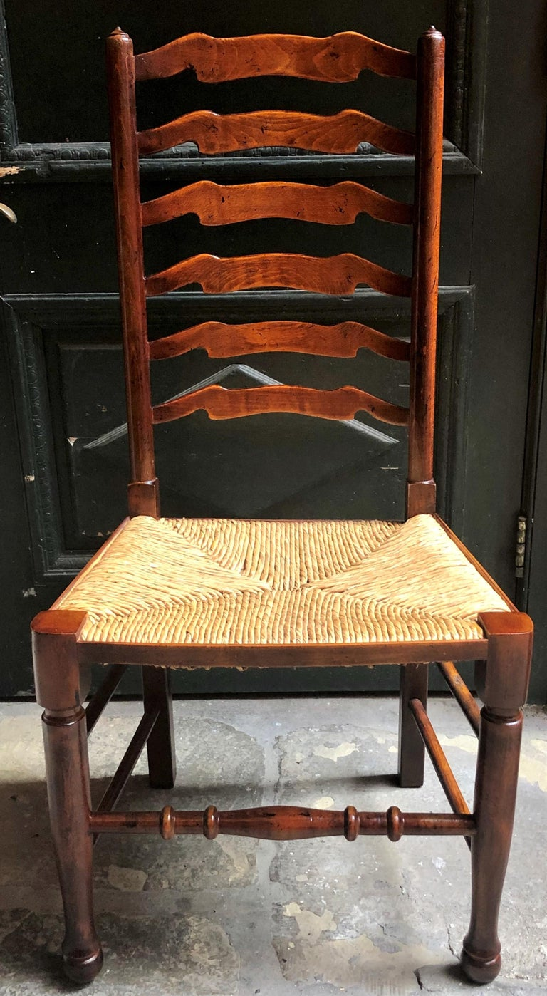 Set of 8 estate English ladder back chairs with rush seats, circa 1940.