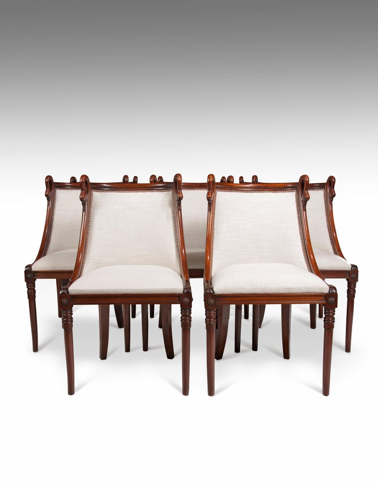 A charming set of 8 French 19th century Empire style barrel back mahogany dining chairs.  French, circa 1880.  Constructed of solid mahogany with a French Empire influence, the sweeping curved barrel backs being flanked by carved swan