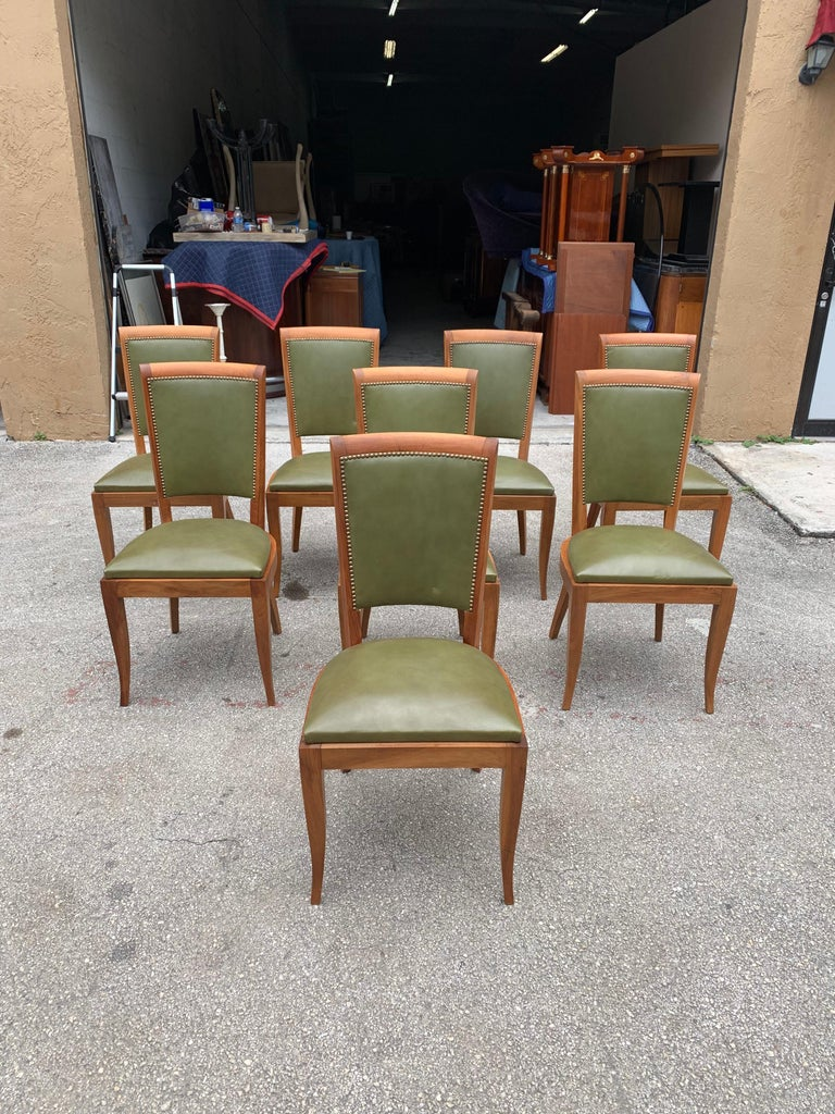 Classic set of 8 French Art Deco dining chairs solid mahogany, the chair frames are in excellent condition. The green leather color is original in very good condition. We travelled to buy all our pieces in France. We bought this beautiful set of 8
