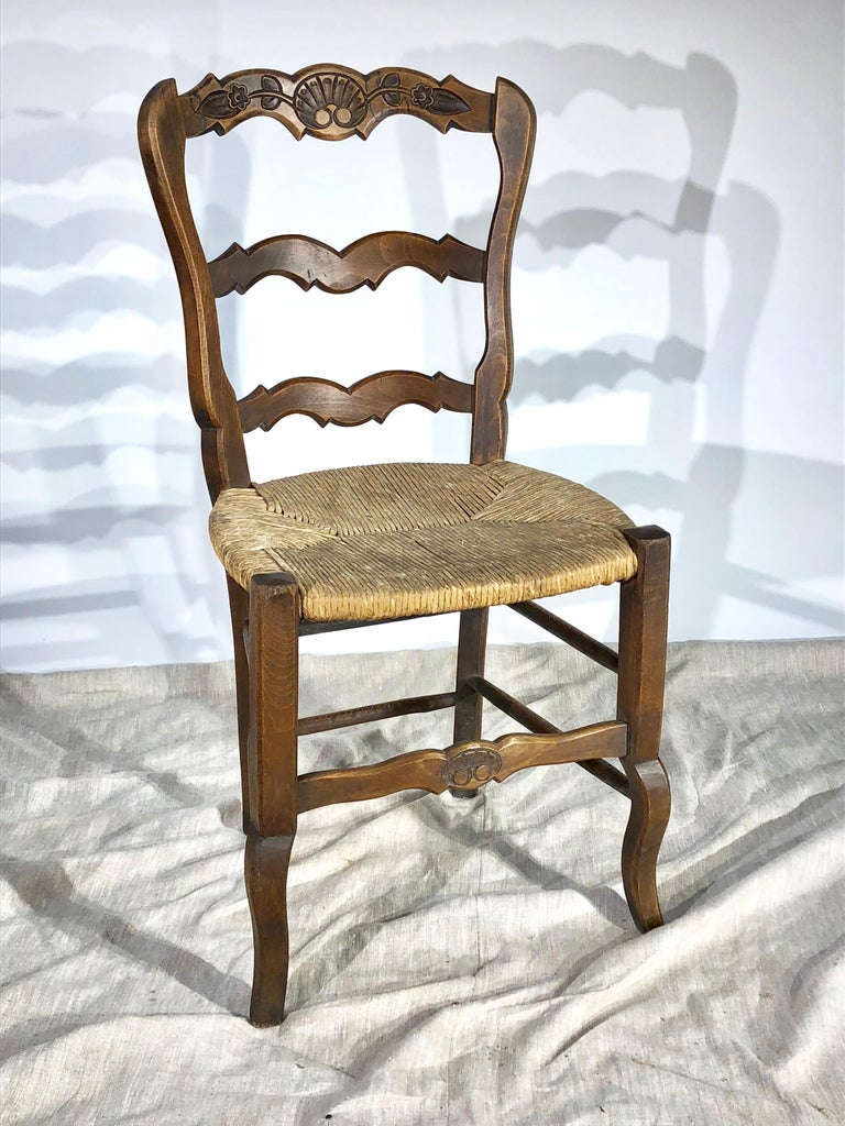 A nice set of 8 ladder-back French County dining chairs, with rush seats and carved back and seat rails, circa 1900. Walnut and oak.