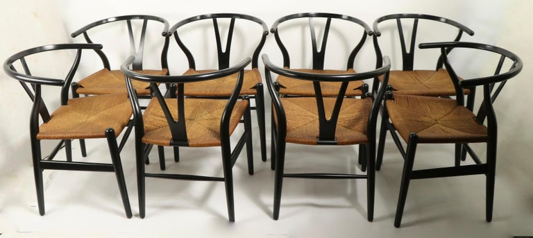 Wonderful set of 8 CH24 chairs designed by Hans Wegner executed by Carl Hansen. These chars are in original black finish with original paper cord seats. All are in very fine condition, showing only light cosmetic wear, normal and consistent with