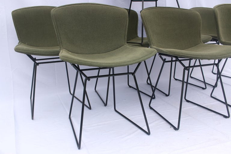 A set of 6 or 8 Harry Bertoia for Knoll black wire chairs with original green seat covers. In good vintage condition - structurally solid, some minor marks to the seat covers and some minor damage to the finish on a the feet of a couple of the