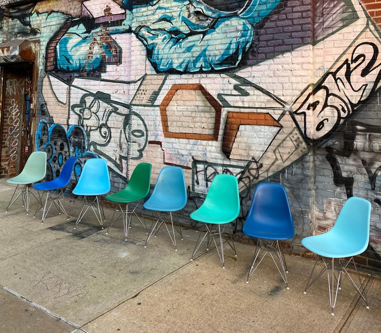 Set of 8 Eames dining chairs for Herman Miller. Spectacular mix of blues and greens. Chairs originally had upholstery that was removed and the original fiberglass shells have been recoated in new colors and clear coat. Brand new chrome aside bases