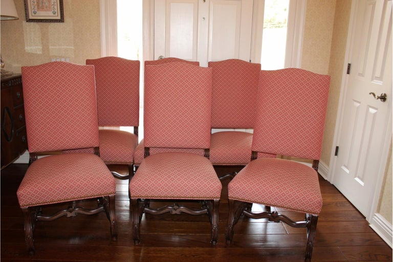 Set of 8 classic carved walnut and upholstered Chippendale style dining chairs, heavy and impressive, with scroll arms decorated with acanthus leaves and beautiful curvy legs and stretchers. 2 Arm chairs, 6 side chairs. Upholstery is a sturdy
