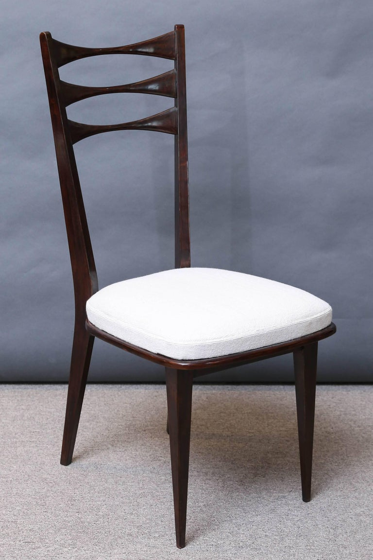 Polished palisander chairs resting on four elegant pointy legs. The sit covered with light beige fabric. Backrest of the chair has two almond shape openings that are carved in curvilinear manner.  Italy, circa 1960s  Measure: 18