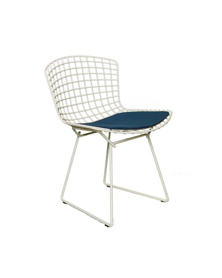 Iconic set of 8 Knoll Bertoia chairs in remarkable condition for age with original blue cushions. These chairs from the fifties were used only as back up a couple of times a year and otherwise were carefully stored. The cushions are all in excellent