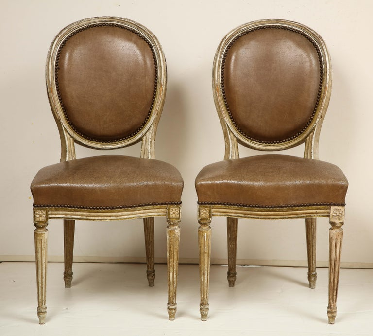 We love the Louis XVI style for its timeless, understated elegance. These eight dining chairs are painted in a soft, creamy white and are upholstered in a rich, brown leather that has aged to perfection! The chairs feature oval backs and details