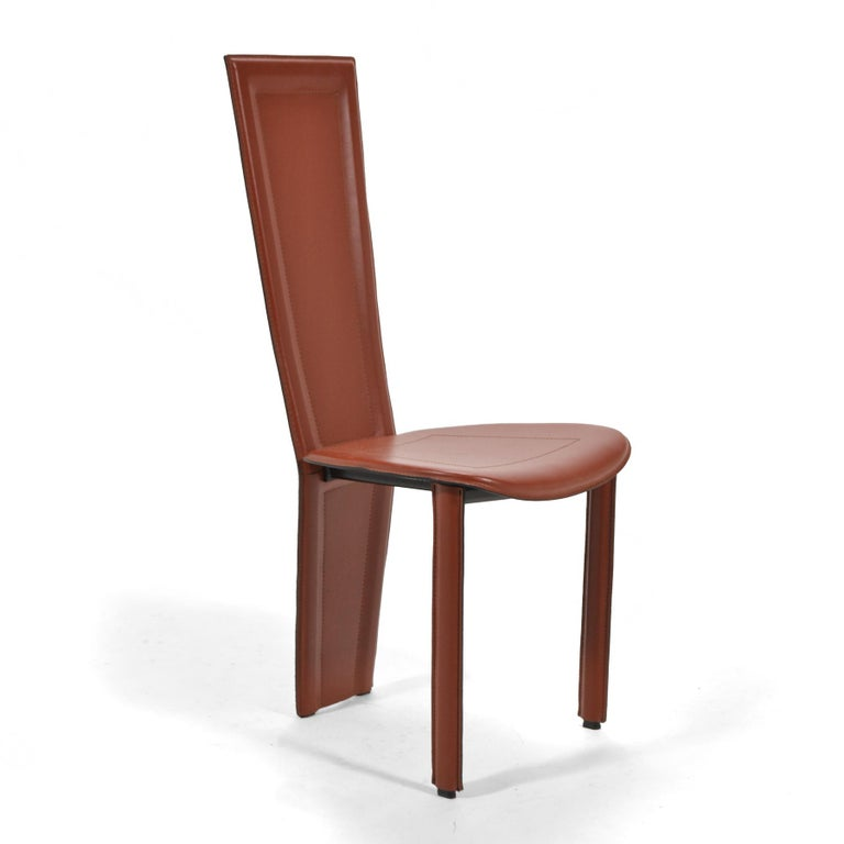 Italian high-style post-modern design, these eight sienna colored leather chairs are elegant and uncommon. Possibly designed by Pietro Costantini, the chairs share qualities with designs by Frank Lloyd Wright and Mario Bellini. The chairs have steel