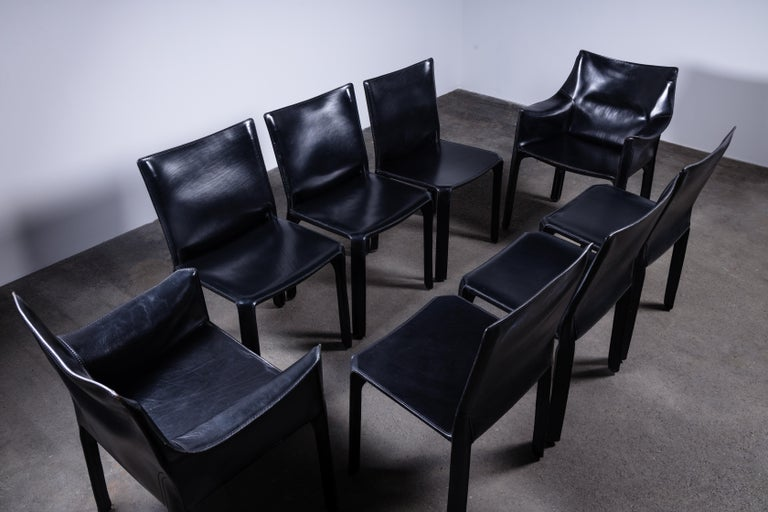 Dining set of 8 Mario Bellini CAB chairs, consisting of two 414 armchairs and six 412 side chairs. Made by Cassina in Italy in the 1980s.  Flexible steel frame covered with a skin of high quality black saddle leather. This elegant, versatile chair