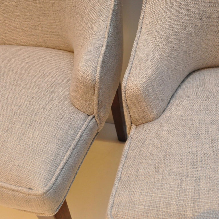 Vintage 1950S-era set of high back upholstered chairs featuring two tall back end chairs and six lower high backs, all newly upholstered in light gray linen. The previous upholsters label had a date of 1966. On one leg of each chair, near the seat's