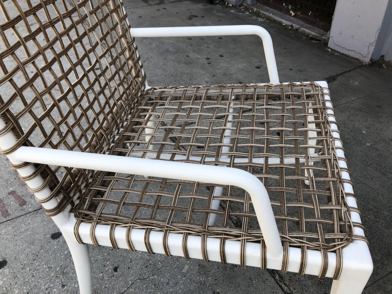 Set of 8 modern arm chairs with steel frames finished in a white powder coated finish and wicker woven seat and backrest.