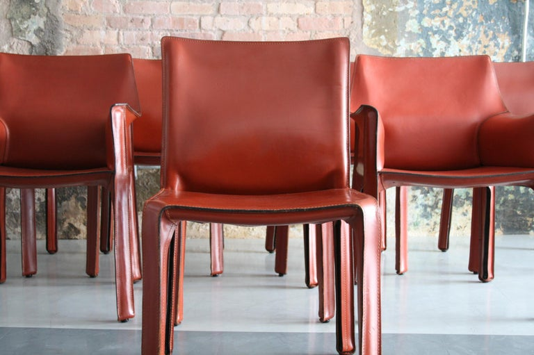 A beautiful set of 8 (2 arm chairs and 6 side chairs) All of them are in fantastic condition with a beautiful rich patina to the red leather. These are an original design by Mario Bellini for Cassina Italy.