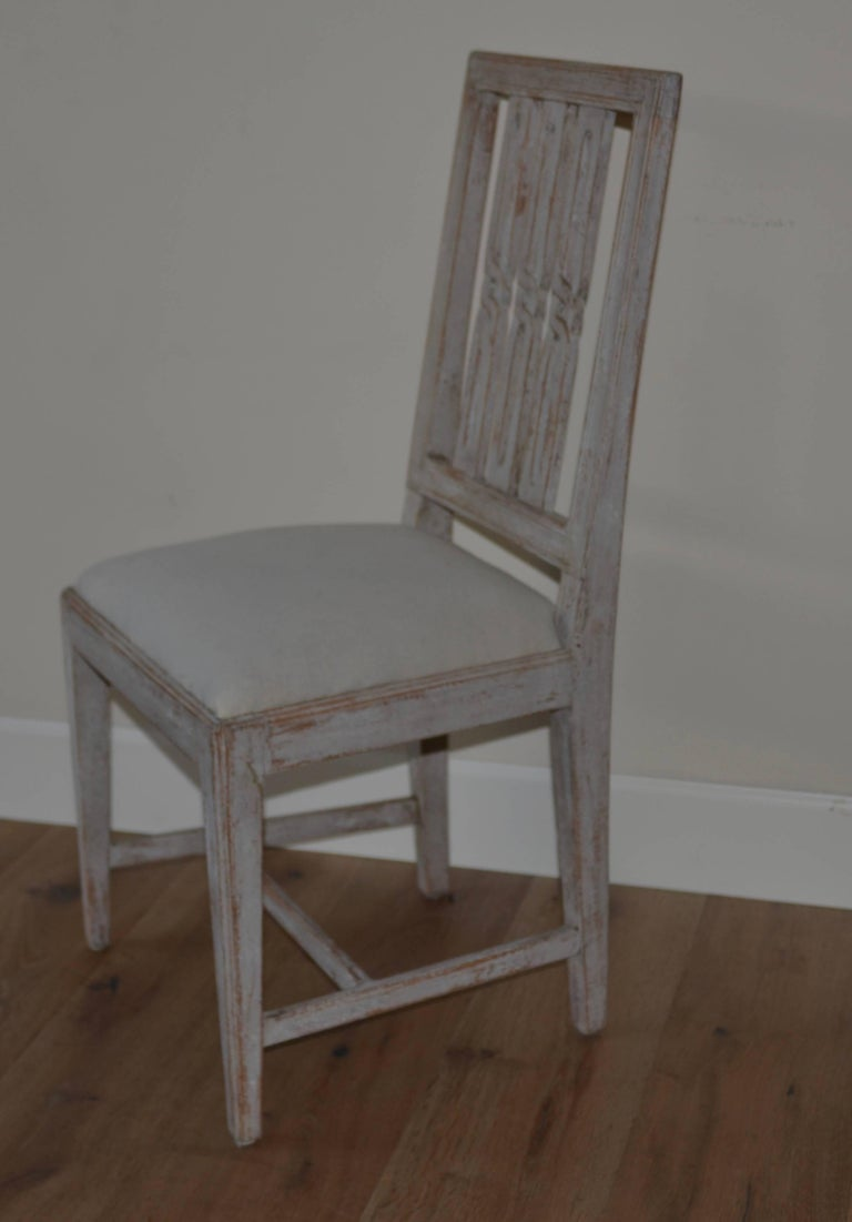 Swedish set of eight period Gustavian dining chairs scraped down to the original Swedish grey/blue finish. Lovely open work geometrical backs with simple tapered legs. Covered in Swedish muslin. Fully restored and sturdy.