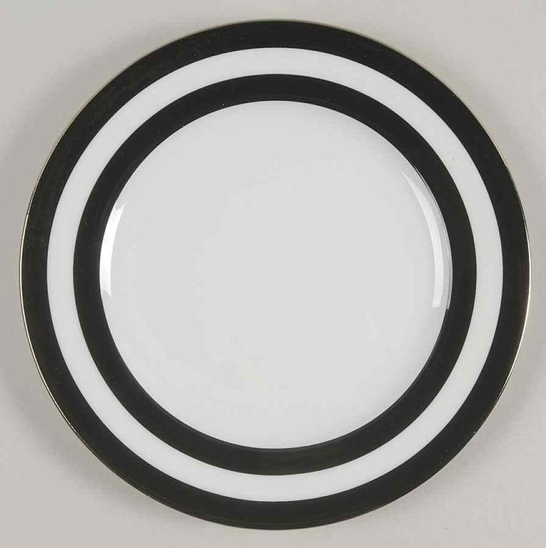 A set of 8 (eight) place settings in the spectator cadet black pattern by Ralph Lauren Home Collection for Wedgwood. Porcelain. Signed, circa 1995-1996.  Features a black border on white with gold rim.   Set of 8 place settings in the black