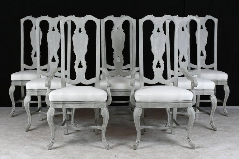 This set of eight 1970s Regency style dining chairs feature carved frames with stretched legs with a pale grey and off-white color combination and distressed finish. The frames have carved details of scrolls and leaves and are finished with cabriole