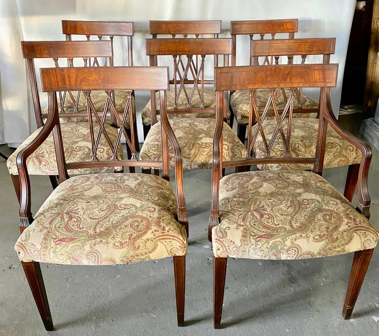 A very elegant set of eight Sheraton Revival mahogany dining chairs, each with beautiful carved X-frame backs. The seats are upholstered in a paisley pattern print, raised on tapering legs. The set consists of 2 arm chairs and 6 side chairs. Arm